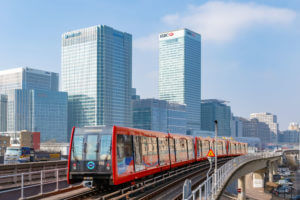 railway train with canary wharf in the background
