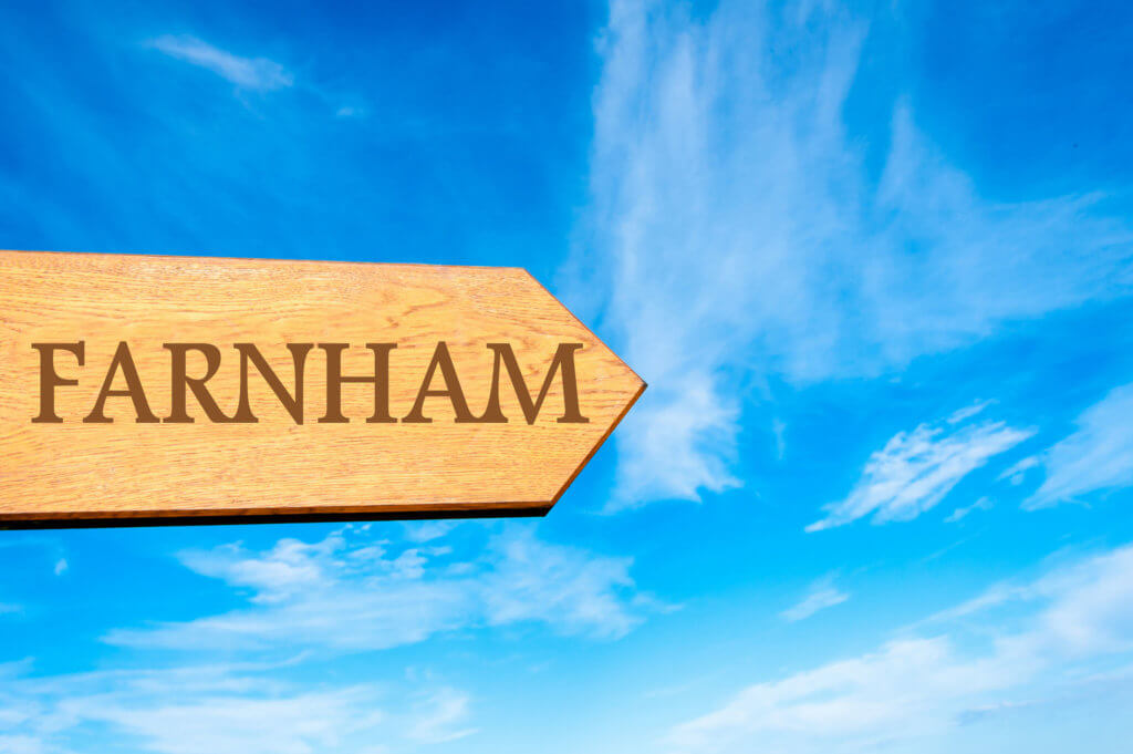wooden arrow sign pointing destination farnham, england