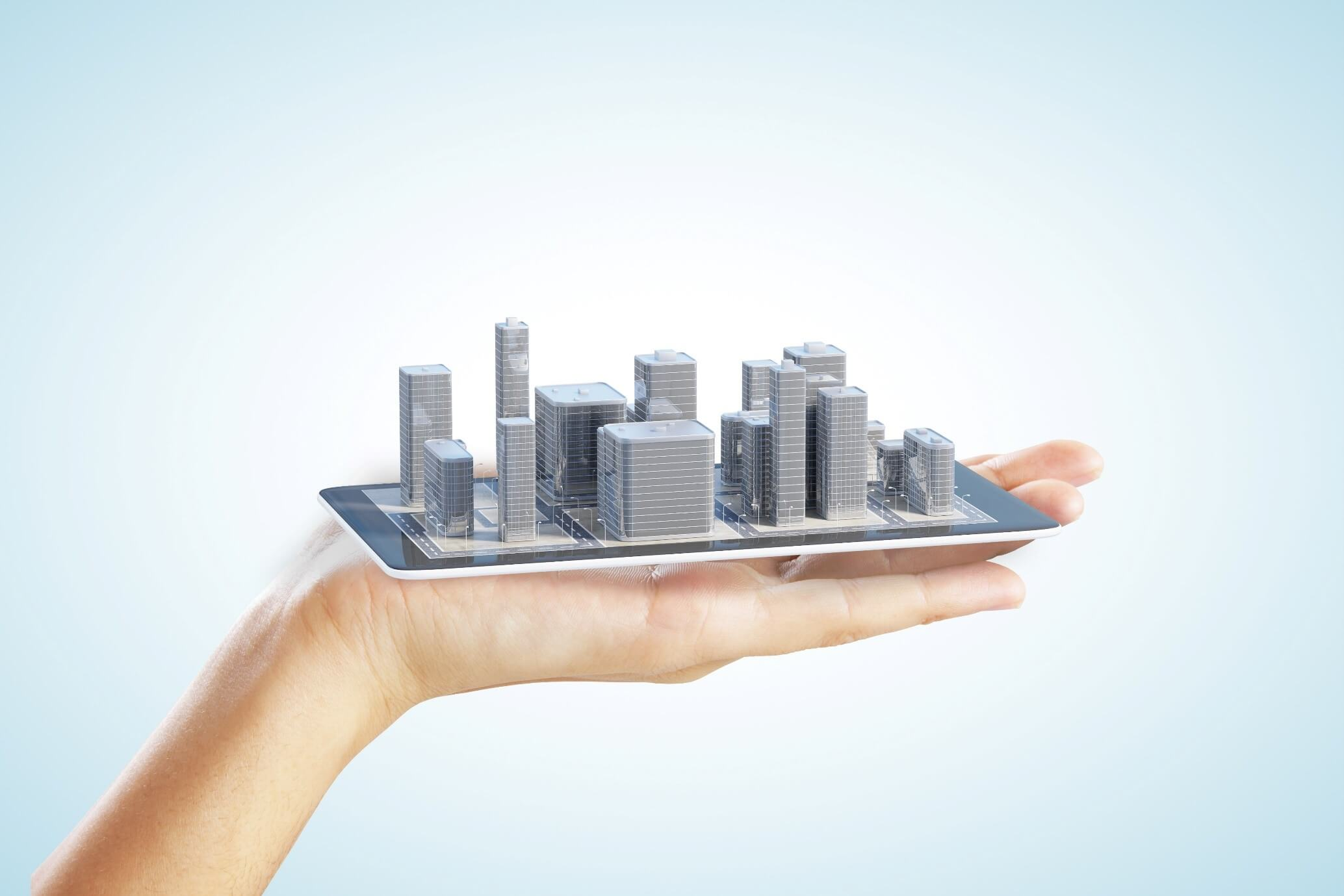 hand holding a tablet with 3d skyscrapers